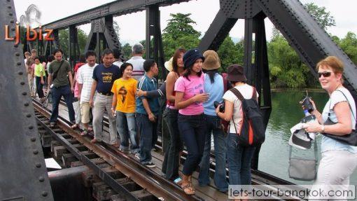 Kanchaburi walking on bridge on river kwai